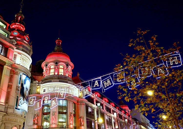 Exterior of Printemps department store in Paris decorated in red, white and green Christmas lights