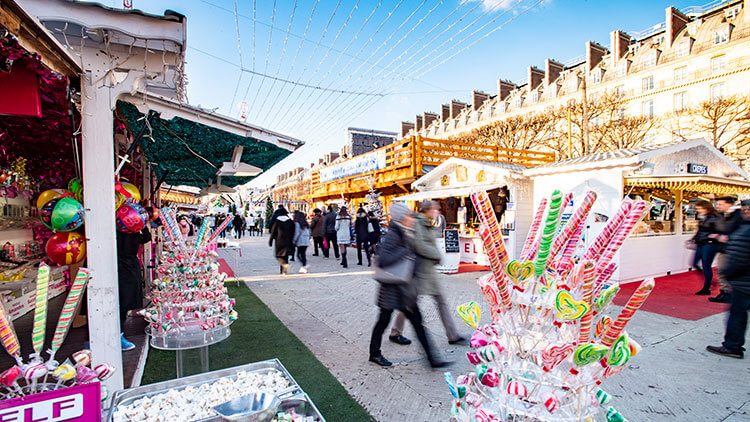 Massive candy canes are sold from one of the wooden huts at the Christmas market in the Jardin des Tuileries in Paris