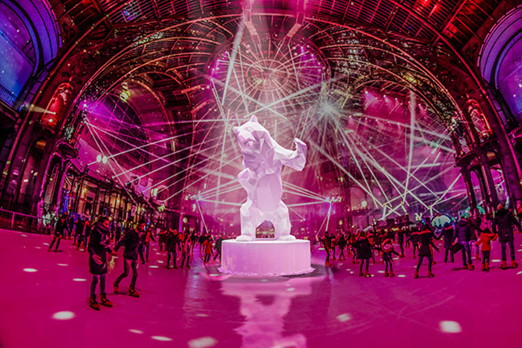 A bear snow sculpture stands in the center of the massive 3000 square meter ice rink at the Grand Palais in Paris, France