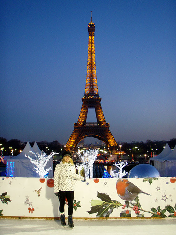 Jen ice skating with a glittering Eiffel Tower as the backdrop at the Champ de Mars Christmas Village in Paris, France