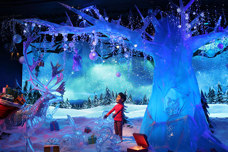 A boy in a fantastical forest filled with icy woodland creatures at Macy's Believe display