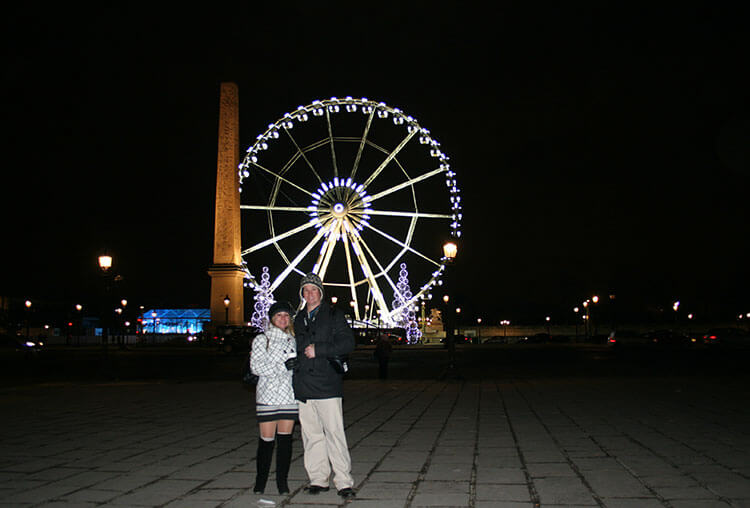 Jen & Tim pose with the Grand Roue a Paris lit up on Place de la Concorde in Paris at Christmas