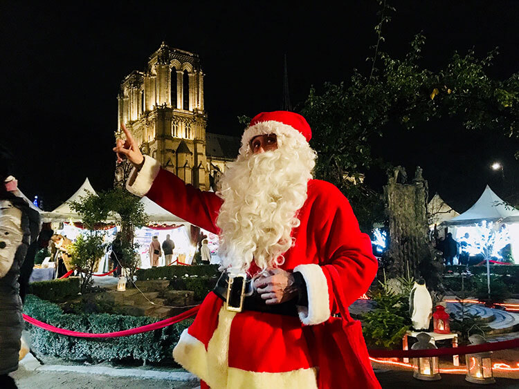 A Santa Claus poses at the Marche de Noel Paris Notre Dame while the cathedral is illuminated behind him