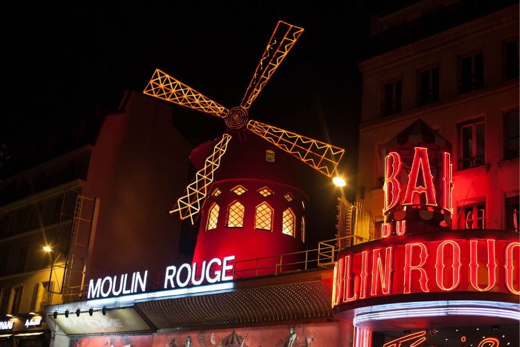 The exterior of Moulin Rouge in Paris, France with the red light windmill