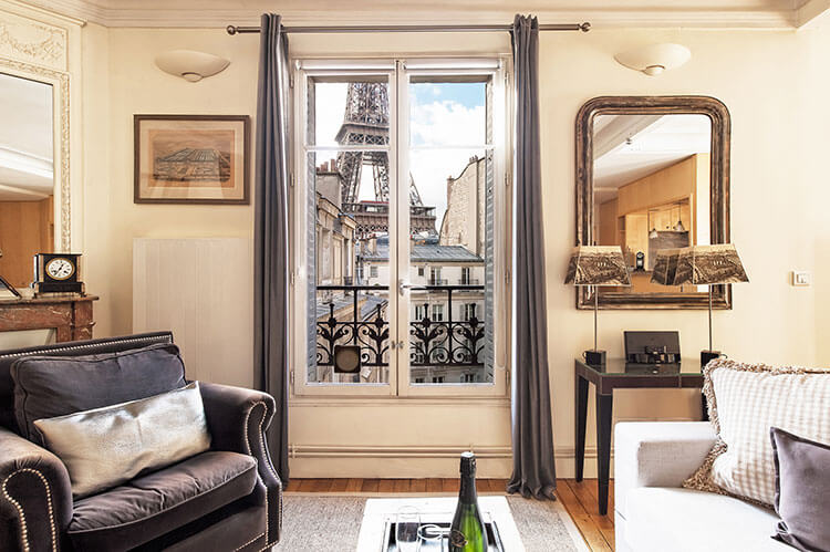 Paris Perfect vacation apartment living room decorated in beige tones with a view of the Eiffel Tower