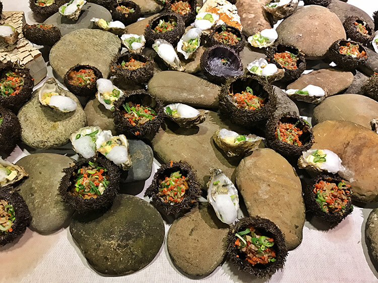 Raw oysters and sea urchin appetizers are arranged on a bed of rocks at Ciné Gourmand