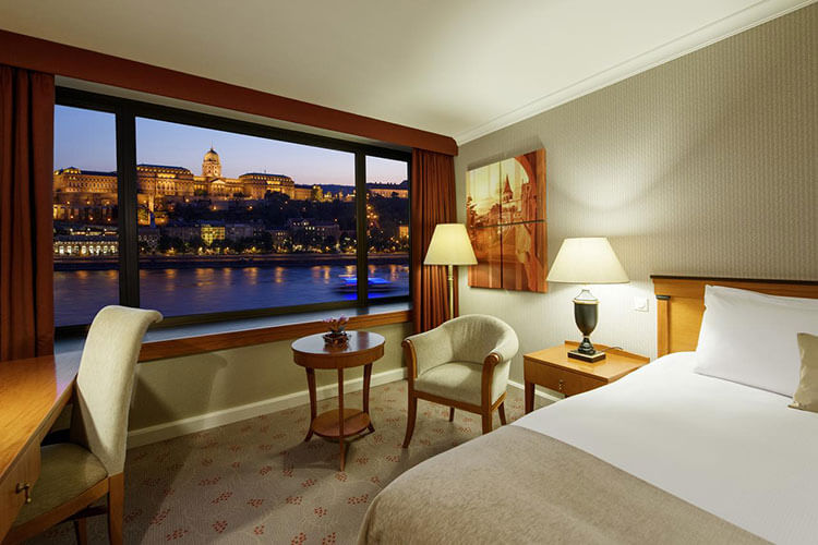 A room at Intercontinental Budapest decorated in beiges and with a huge picture window looking directly across to the Buda castle