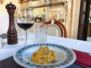 Enjoying carbonara with a glass of wine at In Rome Cooking