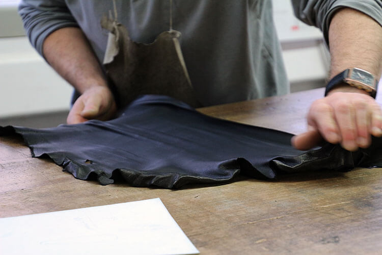 A worker stretches black lambskin as he begins work on a pair of Louis Vuitton driving gloves