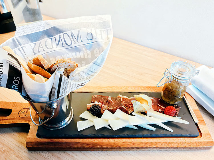A plate of jamon and cheese with kiwi jam and bread
