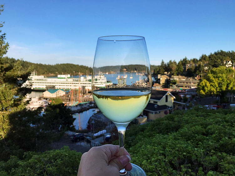 A glass of white wine on the balcony of our room at Friday Harbor House