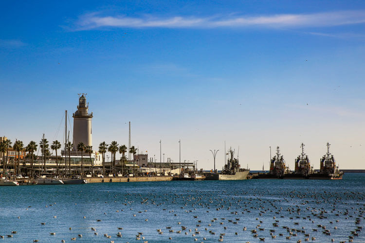 A lighthouse stands at the end of Pier One Port of Malaga