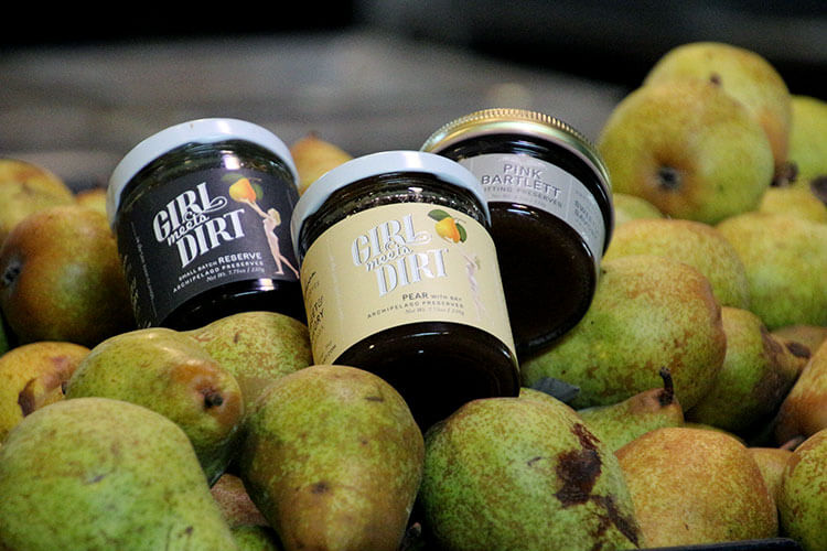 Three jars of pear preserves nestled in pears waiting to be processed