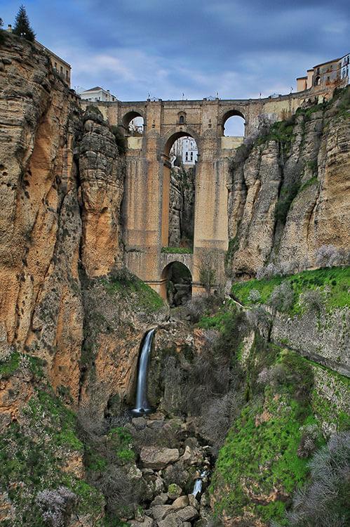 The Puente Nuevo bridge spans the El Tajo gorge and a waterfall falls beneath the bridge