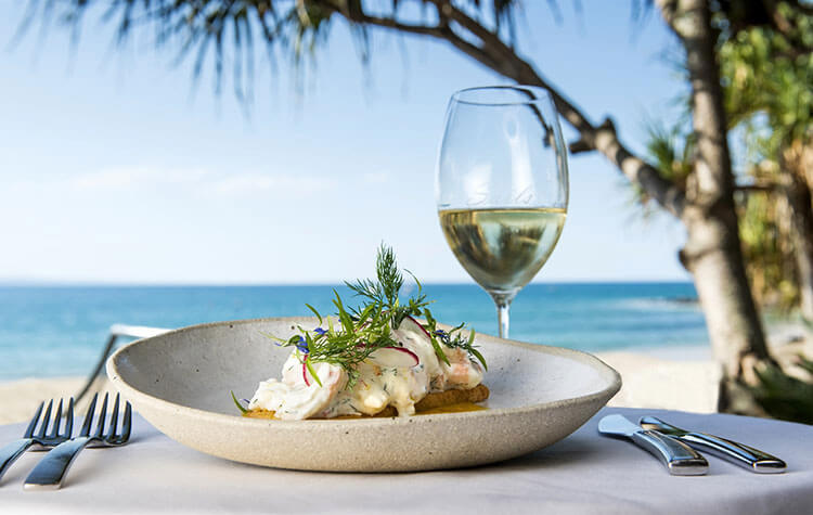 A plate of seafood and a glass of white wine on the beach at the Noose Food and Wine Festival