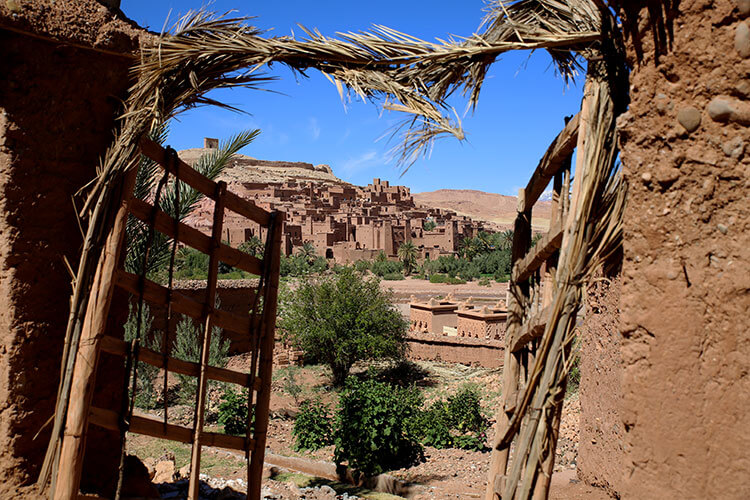 Ait-Ben-Haddou seen from the modern village through a gate made of wood and straw