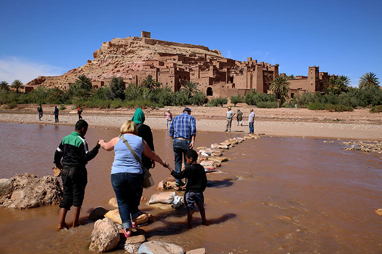 Two Berber children hold Jennifer's hands while she crosses on stones places across the river to Ait-Ben-Haddou