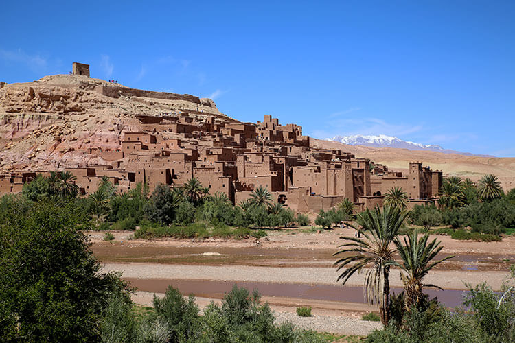 Ait-Ben-Haddou is seen from a distance with the snow-capped High Atlas Mountains behind