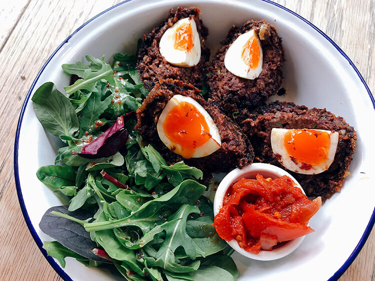 A blood pudding Scotch egg cut in fourths with salad at The Free Press