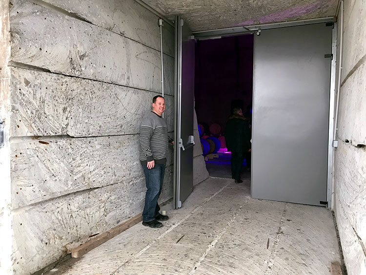 Tim holds open the door to the bunker where you can see how thick the walls are that had to be cut through