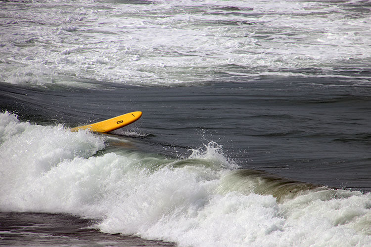 A surfboard tumbles on the waves after a surfer has fallen off