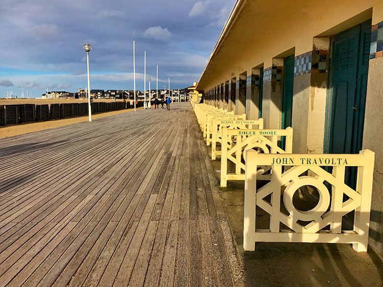 Wooden boardwalk lining the beach with the beach cabins named after American movie starts