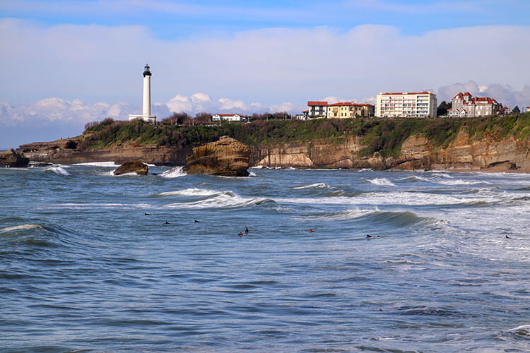 More than a dozen surfers paddle out in the waves at Grande Plage in Biarritz with the lighthouse looming in the distance