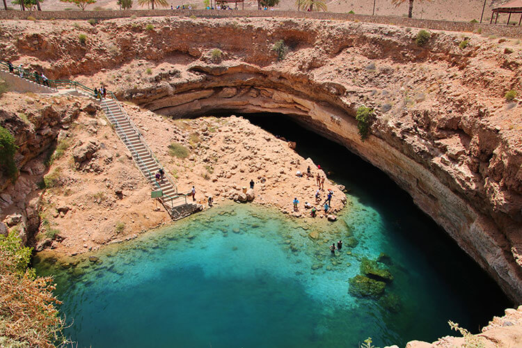 A staircase leads down in to the Bimmah Sinkhole, which is filled with turqouise water