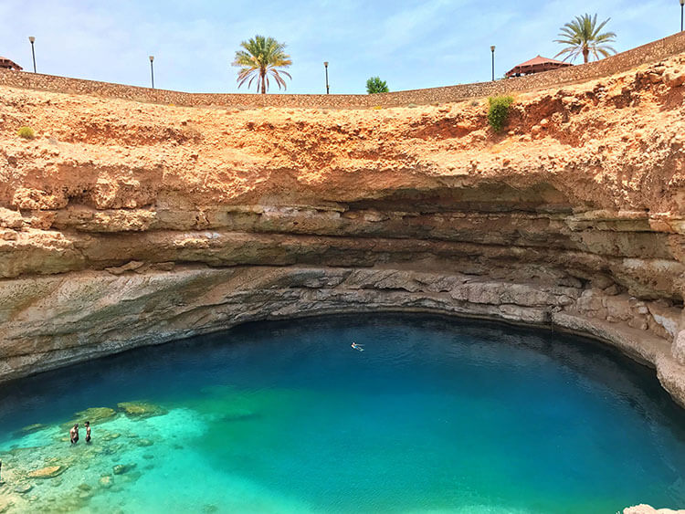 Three people swim in the sinkhole, which is about 70 meters wide