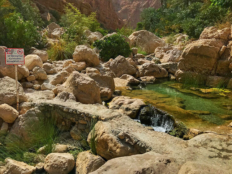 The path at Wadi Shab scrambles over some boulders and passes by small waterfalls