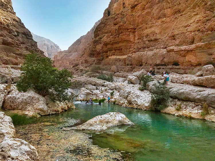 Some people swim in the first pool at Wadi Shab