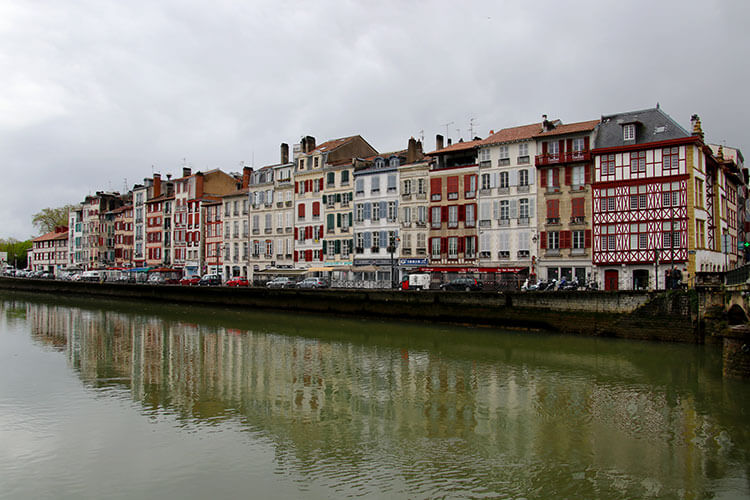 Colorful Basque-style buildings line the river in Bayoone