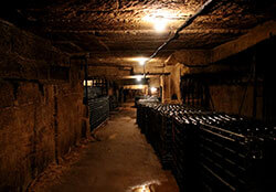 Bottles shelved in baskets line the tunnles of the underground quarry at Château de Bonhoste