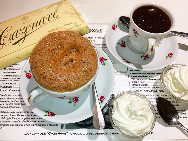 A bar of chocolate, a cup of hot chocolate with a foamy top and a cup of thick pudding-like hot chocolate served with whipped cream