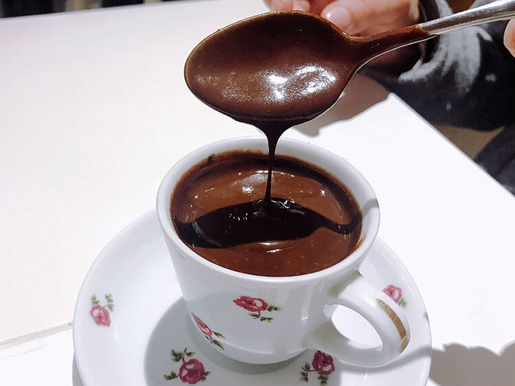 The thick hot chocolate drips slowly from a spoon back in to the espresso-sized cup