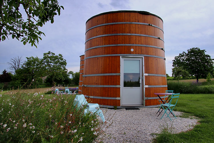 Two giant wine vats sit next to the vines at Château de Bonhoste