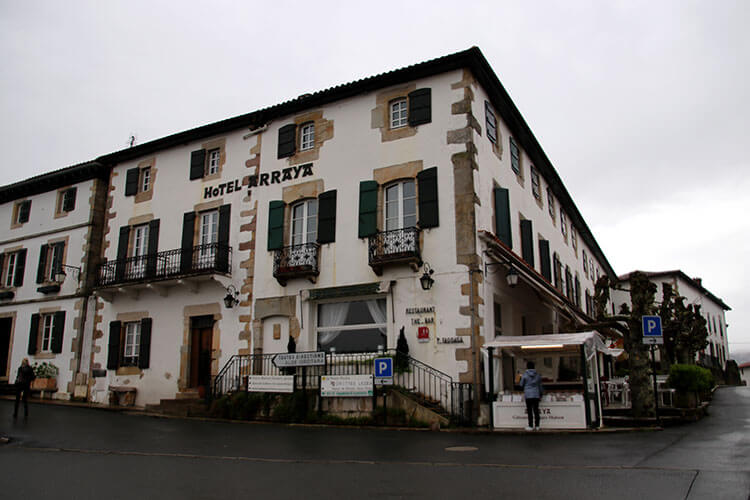 Hotel Arraya is a two-story traditional Basque building with green shutters and balconies set in the center of the village of Sare
