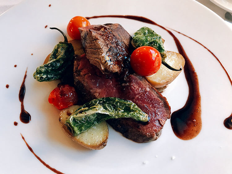 Filet of beef with cherry tomatoes, blistered Padrón peppers and potatoes at Hotel Arraya