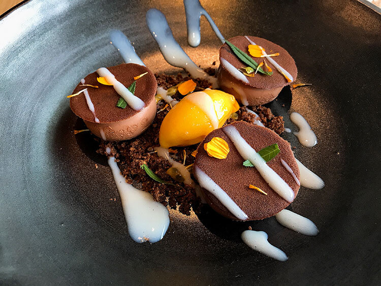 Chocolate mousse is topped with edible flowers and on a bed of chocolate crumble with mango sorbet in the center