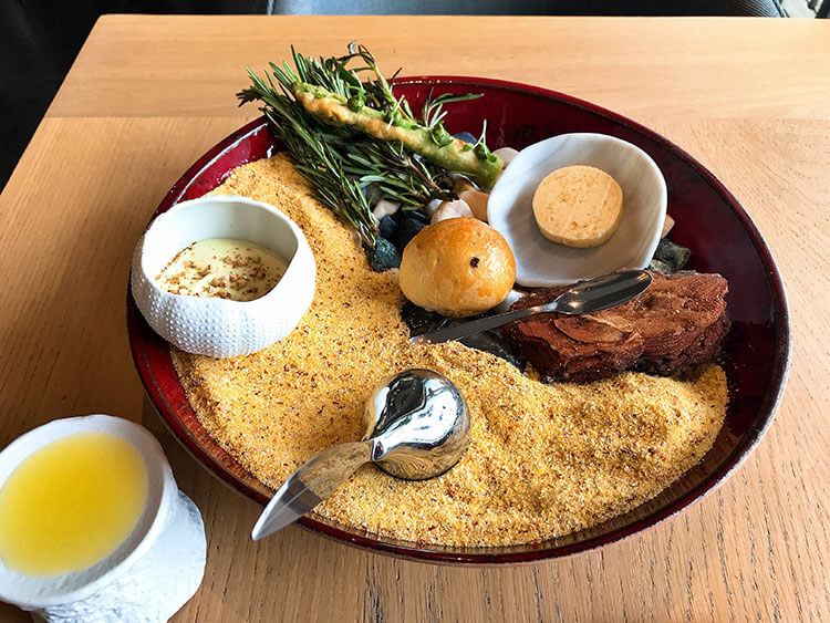 A bowl filled with sand containing an urchin shell filled with a savory tiramisu, a roll, butter and a fried asparagus