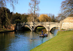 A punt glides down the River Cam behind King's College