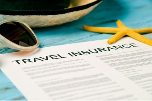 Travel insurance policy, sun hat and sunglasses
