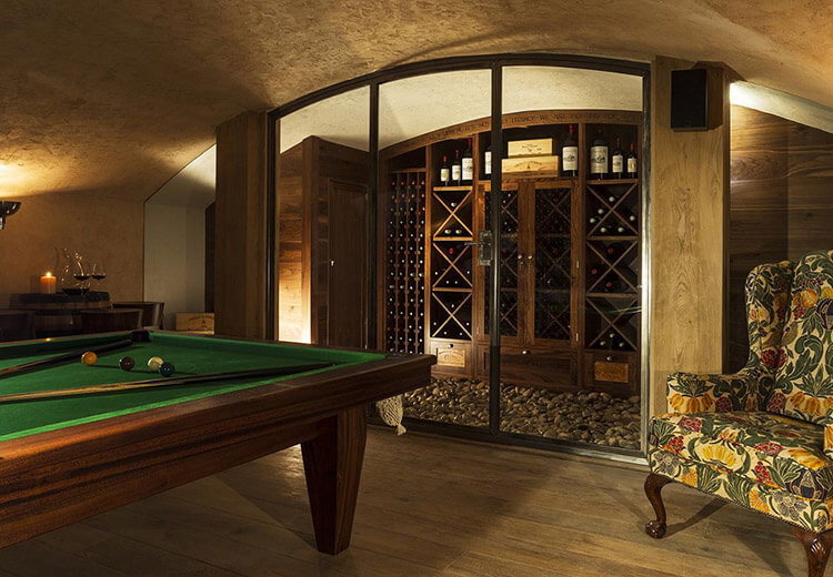 A billard table with the wine cellar behind