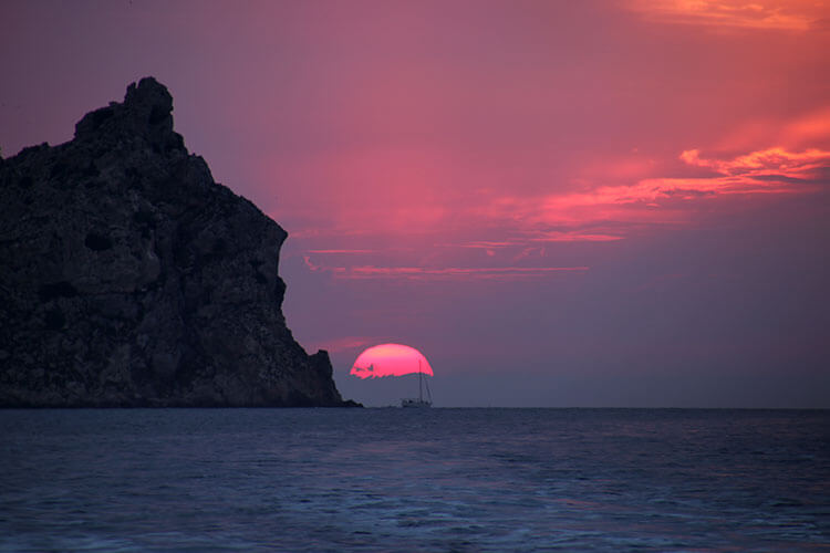 The pink sun just before it's ready to dip below the horizon with Es Vedrà silhoutted
