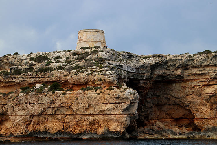 The Torre de sa Punta Prima stands on a rocky cliff of Formentera as seen from the sea