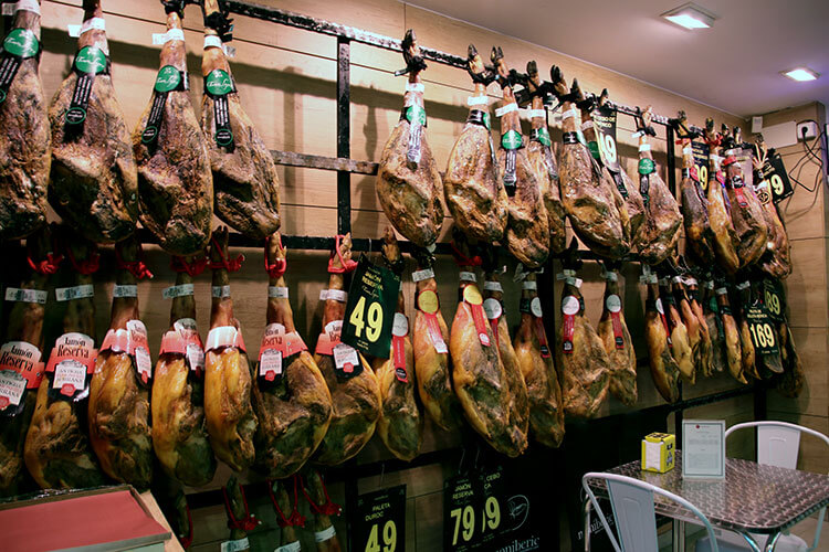 A wall of jamon iberico hanging in a shop in Ibiza
