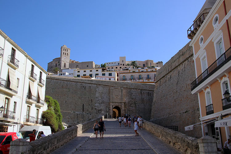 The dramatic main entrance to Dalt Vila slopes upward to a drawbridge flanked by two stone statues