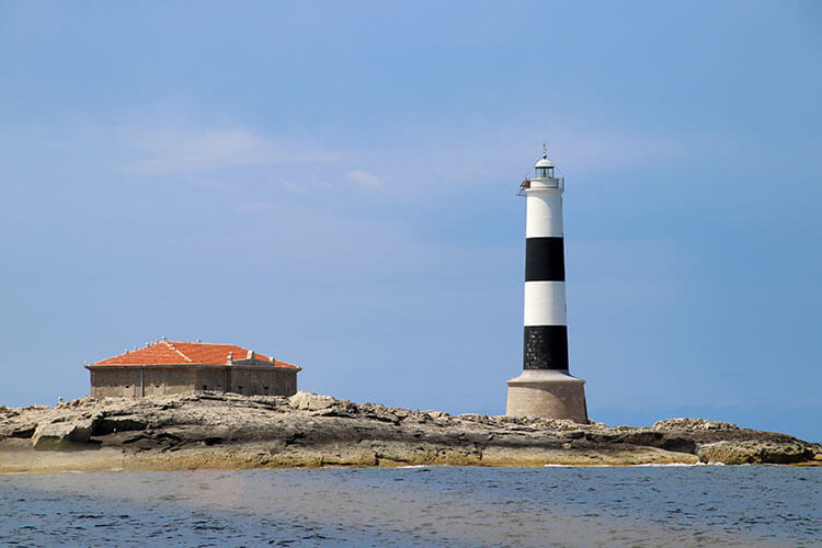 A black and white lighthouse stands on the rocky island Illa des Porcs