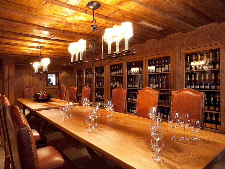 A table with high back chairs sits in the wine cellar at Trofana