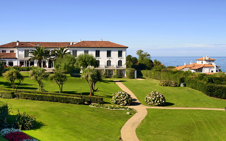 The park and main Basque villa with the ocean beyond at Hôtel la Réserve